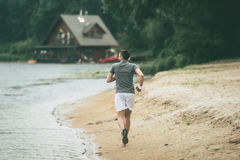 Morning jog. Full length rear view of confident man in sports clothing running along the riverbank Stock Image