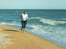 A morning jog women on the shore of the troubled sea. Royalty Free Stock Photos