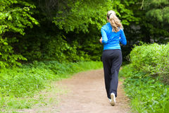 Morning jog for young woman. Young woman running around the park alley Royalty Free Stock Image