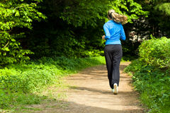 Morning jog for young woman. Young woman running around the park alley Royalty Free Stock Images