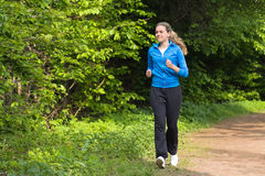 Morning jog for young woman. Young woman running around the park alley Royalty Free Stock Photo