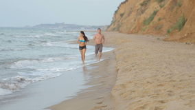 Morning jogging girl and guy along the surf line of the sea beach in summer stock video footage