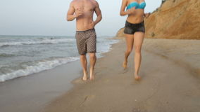 Morning jogging girl and guy along the surf line of the sea beach in summer stock footage