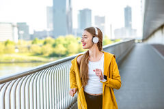Morning jogging in megacity. Young sport woman in yellow sweater with earphones running on the modern bridge with skyscrapers on the background. Morning exercise Royalty Free Stock Photos
