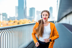Morning jogging in megacity. Young sport woman in yellow sweater with earphones running on the modern bridge with skyscrapers on the background. Morning exercise Stock Images