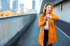 Morning jogging in megacity. Young sport woman in yellow sweater listening to the music with smart watch on the modern bridge with skyscrapers on the background Stock Photos