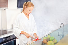 Morning juice in kitchen. Pretty woman making morning juice in kitchen royalty free stock photos