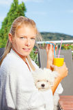 Morning juice on terrace. Woman drinking morning juice on terrace with her dog stock photos