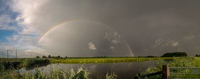 Panorama of a bright colorful rainbow over the dutch countryside. In the morning of 24 July 2017 my son and I chased a rollcloud that moved east over the western stock image