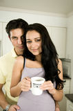 Morning and a Kiss!. An attractive couple enjoys the morning with a kiss and a hot cup of coffee or tea stock image