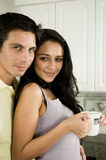 Morning and a Kiss!. An attractive couple enjoys the morning with a kiss and a hot cup of coffee or tea stock photo