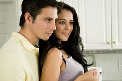 Morning and a Kiss!. An attractive couple enjoys the morning with a kiss and a hot cup of coffee or tea royalty free stock image
