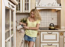 Morning in kitchen. The woman pours the milk into cup. Royalty Free Stock Images
