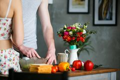 Morning in the kitchen. Young couple preparing meal stock photos
