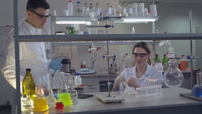 Morning in the laboratory diverse team. Happy smiling scientists preparing to start working. Two people talking wearing sterile blue gloves. Attractive young stock footage