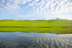 Morning on the lake with green hills and reflection.  Stock Images