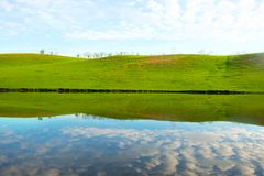 Morning on the lake with green hills and reflection.  Stock Image