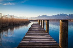 Morning at the lake. A jetty at lake Chiemsee in Bavaria in the morning light Royalty Free Stock Photography