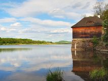 Morning lake with old style wooden fishing hut on the right bank, reflection of sky Royalty Free Stock Images
