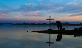 Morning Lake Pray. Man kneeling in pray before a cross, with a morning mist over a lake in the background Royalty Free Stock Images