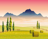 Morning landscape with green field and mountains. Morning autumn landscape with flowering green field, cypress trees and mountains with fog on a pink sky Royalty Free Stock Images