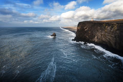 Morning Landscape in Iceland with Rocks in Water and Lighthouse. Ocean Water in Background. Black Sand Beach. Royalty Free Stock Image