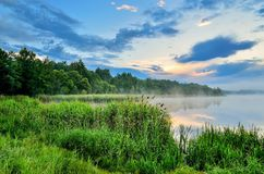 Morning landscape on the lake. Beautiful sky and green grass by the lake stock photography