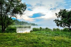 Morning landscape on the lake. Beautiful sky and green grass by the lake royalty free stock photography