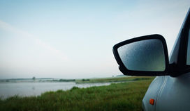 Morning landscape at the lake shore with misted rear view mirror Royalty Free Stock Photography