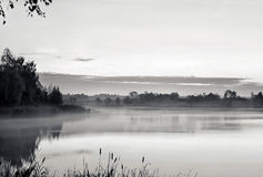 The morning landscape with sunrise over water in the fog. Black Royalty Free Stock Photo