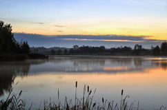 The morning landscape with sunrise over water in the fog Stock Photo
