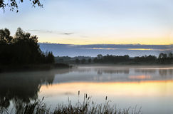 The morning landscape with sunrise over water in the fog Royalty Free Stock Photos