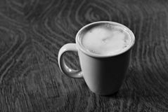Morning latte in black and white. A cup of coffee with foam sitting on a wooden table.  black and white Royalty Free Stock Photography