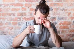 Morning laziness man bed sleepy eyes cup. Morning laziness. Man in bed rubbing sleepy eyes. Time to wake up. Cup of hot drink in hand royalty free stock photos