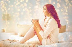 Happy woman with cup of coffee in bed at home. Morning, leisure, christmas, winter and people concept - happy young woman with cup of coffee or tea in bed at Royalty Free Stock Image