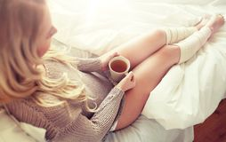 Close up of woman with tea cup in bed stock photo