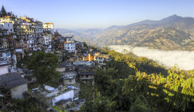 Morning Light on a Small Village. Morning light reflects off the small buildings in the town of Yuanyang, China as an iversion layer of fog fills the deep valley Stock Images