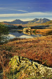 Morning light, Snowdon range, Wales. A view of the Snowdon range, taken from beside Llynnau Mymbyr, Capel Curig, North Wales. Overlooking a large boulder Stock Image