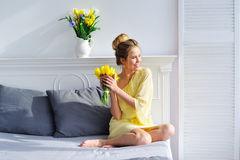 Morning light and woman with yellow tulips Stock Images