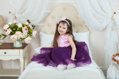 Morning of little princess. Cute girl in her light and cozy bedr. Oom. Flowers for child`s holiday Royalty Free Stock Photo