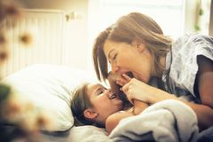 Morning a lot of fun and laughter. Young mother with her little daughter in bed. Space for copy royalty free stock photography