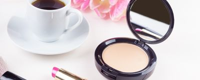 Panoramic mocap with a cup of coffee, powder and lipstick, feminine morning background. Morning makeup products - panoramic mocap with a cup of coffee, powder stock image