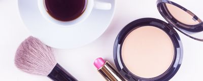Panoramic mocap with a cup of coffee, Cake, powder and lipstick, female morning background. Morning makeup products - panoramic mocap with a cup of coffee royalty free stock photo