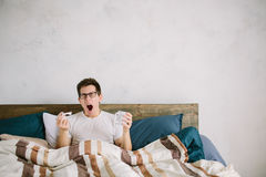 Morning. Man lies in bed. He holds in his hand a napkin and cup of tea or coffee. The guy does not get enough sleep royalty free stock image