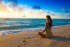 Morning Meditation. A woman meets the sun early morning by the sea with meditation stock photo