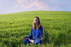 Morning meditation. The girl is fond of Oriental Culture and meditates on the meadow Royalty Free Stock Photos