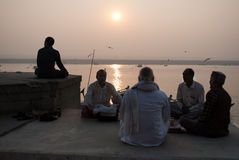 Morning Meditation. A group of Indian men are doing meditation in the early morning on the river bank at Varanasi, India. Many people engage themselves in Stock Image