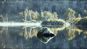 Morning mist on calm lake with rock. Mist clears from a calm wilderness lake in Tasmania's Cradle Mountain National Park stock video footage