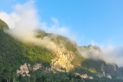 Morning mist on the forested cliffs by the lake Cheow Lan Royalty Free Stock Photo
