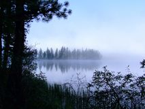 Morning mist on a mountain lake. Stock Photo